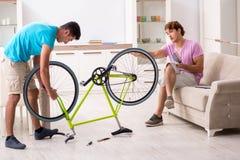 L'homme réparant sa bicyclette cassée photo libre de droits