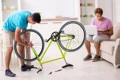 L'homme réparant sa bicyclette cassée image stock