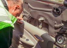 L'homme répare la porte de sa voiture image stock