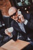 L'homme réussi sérieux appelle par le mobile et apprécie son café photo libre de droits