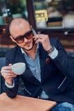 L'homme réussi sérieux appelle par le mobile et apprécie son café photos stock