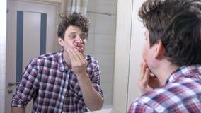 L'homme réveillé somnolent fatigué avec une gueule de bois dans la salle de bains, regarde le miroir banque de vidéos