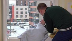 L'homme réveillent sa fille d'enfant dormant sur le radiateur près de la fenêtre et du baiser neige banque de vidéos