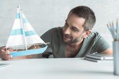L'homme raidi joyeux tient peu de bateau photo libre de droits