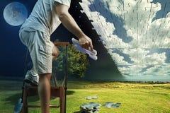 L'homme rassemble le ciel des puzzles tout en se tenant sur l'échelle photo stock