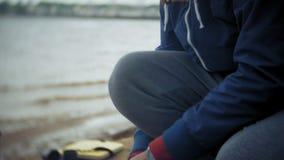 L'homme rassemble une tente de touristes sur la banque de la rivière de la mer clips vidéos