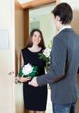 L'homme reçoit un cadeau d'une femme et des fleurs Photographie stock libre de droits