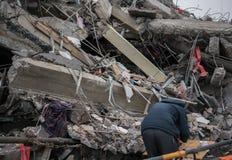 L'homme recherchant des marchandises dans des ruines détruites modernes de bâtiment se ferment Photographie stock libre de droits