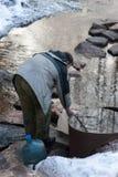 L'homme recueille l'eau dans une boîte métallique Image libre de droits