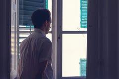 L'homme regarde la fenêtre d'une chambre noire Images stock