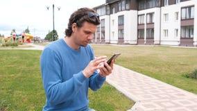 L'homme regarde les réseaux sociaux sur l'écran d'un téléphone portable banque de vidéos