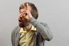 L'homme regarde par un ok de signe Photographie stock libre de droits