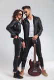 L'homme regarde sa femme tout en tenant la guitare électrique Image libre de droits