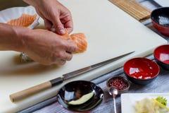 L'homme remet le petit pain de sushi Photo stock