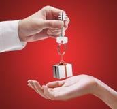 L'homme remet une clé de maison à un femme. Image libre de droits