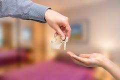L'homme remet une clé de maison à un femme blanc réel d'isolement par maison de patrimoine du dollar de concepts image stock