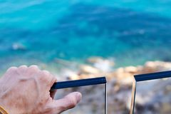 L'homme remettent le rail devant la mer photographie stock