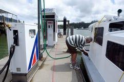 L'homme remplit de combustible son bateau Photographie stock libre de droits