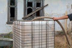 L'homme remplit réservoir en plastique avec de l'eau images stock