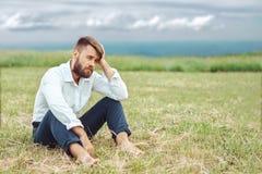 L'homme repose triste sur l'herbe image stock