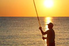 L'homme reste à terre avec la pêche-tige et les poissons Photos stock