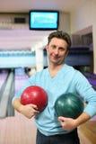 L'homme reste et retient deux billes pour le bowling Photographie stock