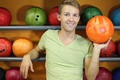 L'homme reste les étagères proches avec des billes dans le club de bowling Photos libres de droits
