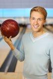 L'homme retient la bille rouge dans le club de bowling Photos libres de droits