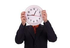 L'homme retient une horloge Photographie stock