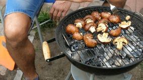 L'homme retournent les grands champignons délicieux de champignon de paris, qui rôtissent au-dessus des charbons sur le barbecue banque de vidéos