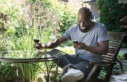 L'homme rit le message textuel de lecture dans le jardin Images stock