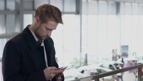 L'homme roux regarde le téléphone sur l'Internet dans le couloir dans le manteau, mouvement lent clips vidéos