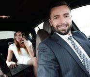 L'homme sérieux élégant attirant conduit la bonne voiture image stock