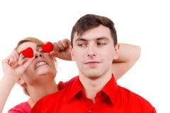 L'homme sérieux et la femme folle tient les coeurs rouges au-dessus des yeux Photographie stock