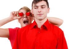 L'homme sérieux et la femme folle tient les coeurs rouges au-dessus des yeux Images stock