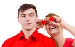 L'homme sérieux et la femme folle tient les coeurs rouges au-dessus des yeux Photos libres de droits