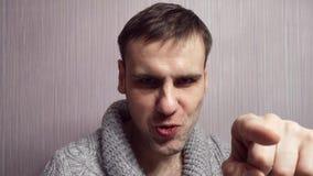 L'homme sérieux pousse son doigt dans la caméra, et puis montre son doigt et sourires banque de vidéos