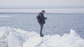 L'homme sûr portant une position chaude de manteau sur le glacier redresse ses cheveux et le regard loin Nature stupéfiante d'a clips vidéos