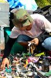 L'homme s'accroupit et examine des montres lancent sur le marché indirectement Image stock