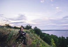 L'homme s'asseyant sur la banque de la rivière au lever de soleil et contemple le beau paysage Images stock