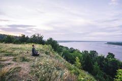 L'homme s'asseyant sur la banque de la rivière au lever de soleil et contemple le beau paysage Photos libres de droits