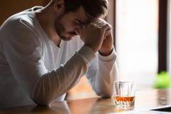 L'homme s'asseyant sur le compteur de barre sent la boisson potable déprimée d'alcool photos libres de droits