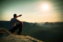 L'homme s'asseyent sur le bord de roche Le randonneur fait l'ombre avec la main et la montre à la brume colorée en vallée de forê Images stock