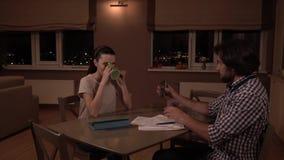 L'homme s'assied à la table avec la femme Il prend des papiers et les remet Le type obtiennent la calculatrice et les expositions banque de vidéos