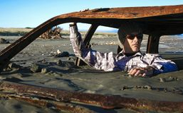 L'homme s'assied dans l'épave rouillée de voiture enterrée en sable sur la plage Images libres de droits