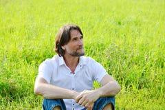 L'homme s'assied dans l'herbe pendant l'été Image libre de droits