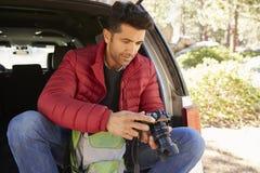 L'homme s'assied dans le dos nu de la voiture dans la forêt vérifiant l'appareil-photo Images stock