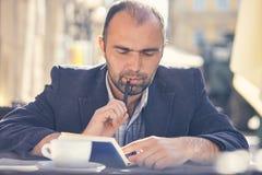 L'homme s'assied dans un café et des notes dans un carnet Images libres de droits