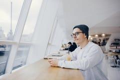 L'homme s'assied devant la table près de la fenêtre Images libres de droits