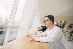 L'homme s'assied devant la table près de la fenêtre Photographie stock